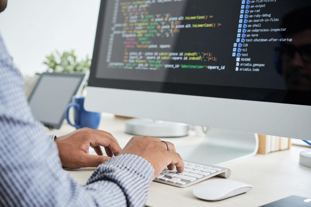 プログラミングコードを書いているエンジニア男性の手元